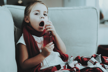 Little Girl with Cold in Red Scarf Using Spray. Sick Young Girl. White Sofa in Room. Unhappy Child. Disease Concept. Healthcare and Healthy Lifestyle Concept. Little Girl at Home. Stock Photo