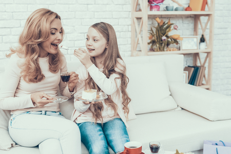 Happy Family Celebrating Birthday and Eating Cake. Cake on Table. Happy Family. Mother with Daughter. Smiling Women at Home. Celebration Concept. Plate in Hands. Cute Girl. Cake Feeding.
