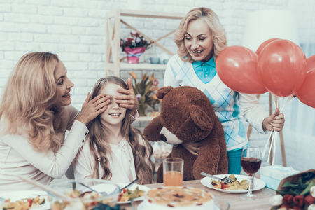 Family Preparing Surprise for Daughter at Home. Cake on Table. Happy Family. Mother with Daughter. Smiling Women. Smiling Grandmother. Celebration Concept. Toy Bear. Closed Eyes. Red Baloons.