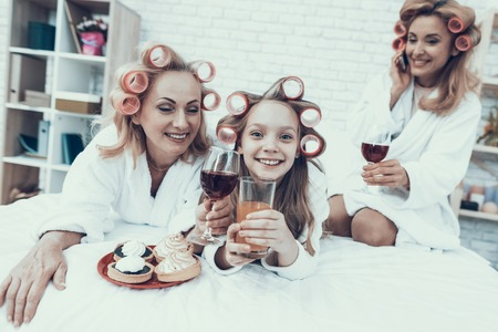 Women in White Bathrobes Eating Cakes and Drinking Have Fun at Home. Happy Family. Mother with Daughter. Smiling Women. Lying on Sofa. Have Fun Indoor. White Sofa. Family after Bath. Womens Beauty Concept.