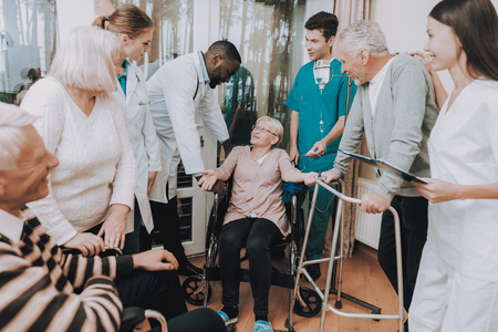 Smiling Medical Staff. Patient with Walker. Nursing Home. Sitting Woman with Medical Dropper. Doctor in Nursing Home. Man with Crutches. Patient on a Wheelchair. Smiling Pensioner Rehabilitation.