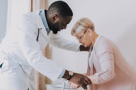 Le docteur aide la femme à se lever. Le patient se sent malade. Docteur souriant. Le médecin examine un patient âgé. Femme Parlez de son état. La femme essaie de se lever. Maison de repos. Le docteur interroge une femme.