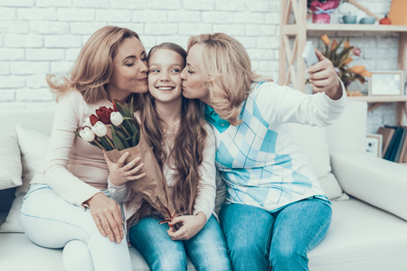 Happy Family Taking Selfie on Daughters Birthday. Happy Family. Mother with Daughter. Smiling Women. Smiling Grandmother. Celebration Concept. Using Smartphone. Taking Photo. Bouquet in Hands.