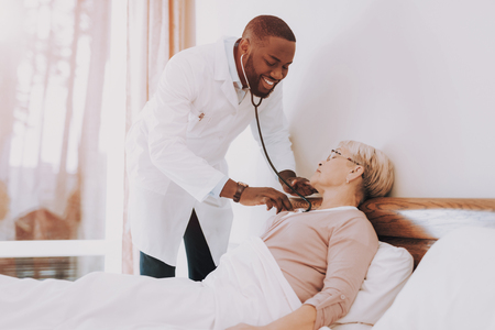Woman Lay in Bed. Doctor Examines Elderly Patient. Doctor Measures Pulse and Pressure. Women Tell about her Condition. Smiling Doctor. Nursing Home. Patient Feel Sick. Doctor Interviews Woman.