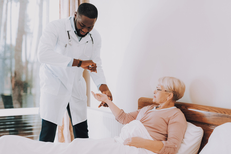 Doctor Measures Pulse and Pressure. Woman Lay in bed. Women Tell about her Condition. Smiling Doctor. Doctor Examines Elderly Patient. Nursing Home. Patient Feel Sick. Doctor Interviews Woman.