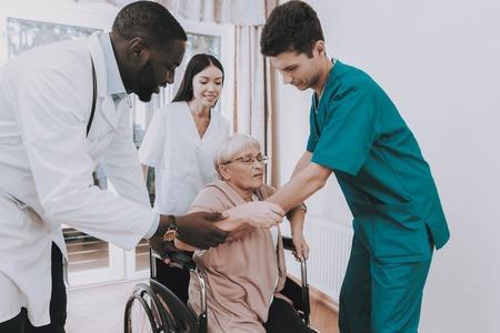 Une femme âgée se met en fauteuil roulant. La femme se sent faible. L'infirmière aide la femme à sortir du lit. Maison de repos. Docteur en Clinique. Le docteur aide le patient à se lever. Patient en fauteuil roulant. Pensionné en réadaptation. Banque d'images