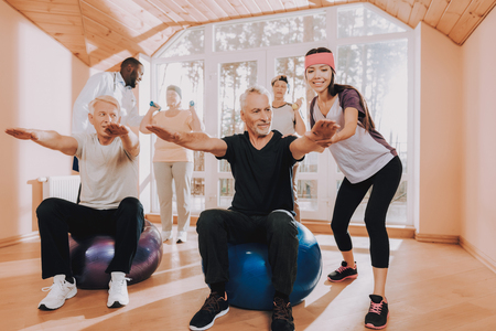 Men do Exercises Fitness Balls. Patient in Sport Uniform. Active Retiree Nursing Home. Instructor Show Exerscises. Elderly People Engaged. Therapeutic Gymnastics. Old People Healthcare Lifestyle.