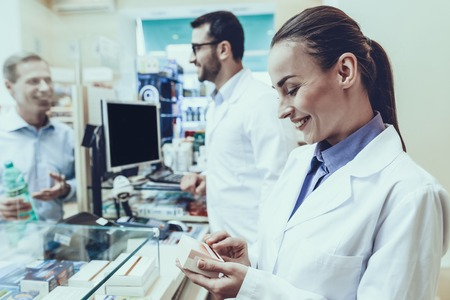 Pharmacists Working at Counter. Man Buys Mineral Water at Male Pharmacist. Female Pharmacist Holding Box with Medicaments. Pharmacists Wearing Medical Uniform. People Located in Pharmacy.