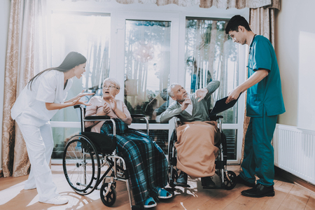 Bad Service in Nursing Home. Very Emotional Talk. Elderly People Very Frightened. Medical Workers Argue with Elderly Couple. Pensioner Sitting in Wheelchair. Awful Current Affairs in Hospital. Фото со стока