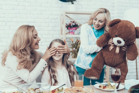 Family Preparing Surprize for Daughter at Home. Cake on Table. Happy Family. Mother with Daughter. Smiling Women. Smiling Grandmother. Celebration Concept. Toy Bear. Closed Eyes. Plush Toy. Stock Photo - 115162111