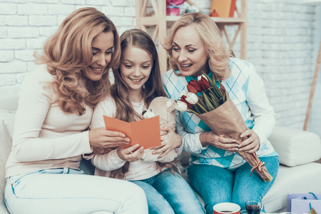 Family Celebrating Mothers Birthday at Home. Cake on Table. Happy Family. Mother with Daughter. Smiling Women at Home. Smiling Grandmother. Celebration Concept. Cup of Tea. Toy Bear. Stock Photo