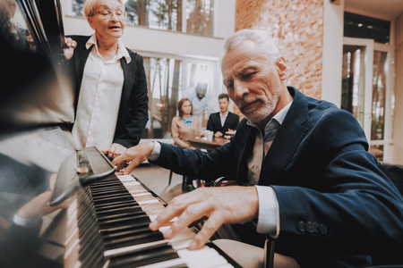 Elderly Man Plays the Piano. Doctor at Head of Table. Nursing Home. Elderly Woman Stay Near. Young People Sit at Table. Cute Relationship. Happy Holidays. Happy Together. Smiling People.