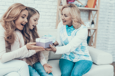 Grandmother Giving Gift Boxes to Family at Home. Mother with Daughter. Smiling Women. Celebration Concept. Happy Family. Sitting at Home. Holiday in March. White Sofa. Happy Daughter. Stok Fotoğraf