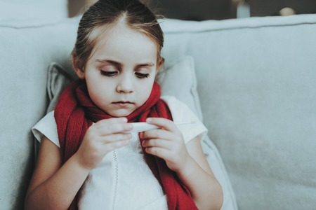 Girl with Cold in Red Scarf Checking Temperature. Sick Young Girl. White Sofa in Room. Unhappy Child. Disease Concept. Healthcare and Healthy Lifestyle Concept. Little Girl at Home.