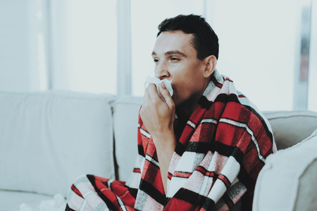 Man with Cold Sitting on Sofa in Checkered Blanket. Man at Home. Sick Young Man. White Sofa in Room. Unhappy Guy. Disease Concept. Healthcare and Healthy Lifestyle Concept. Using Napkins. Stock Photo
