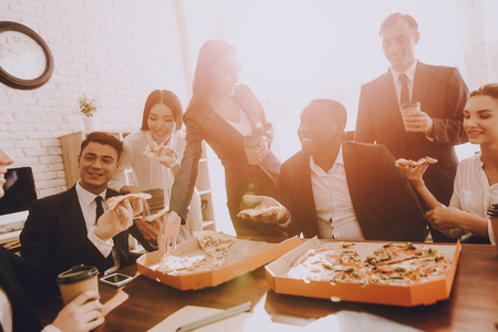 Team of Managers Have Lunch in Modern Office. Rest after Business Meeting. Modern Office Concept. Cooperation with Colleagues. Businessman with Team. Pizza in Box. Businessman in Suit. Stok Fotoğraf