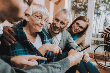 Grandchildren and Grandparents Sitting on Couch. Family Watch Something on Tablet. Nursing Home. Senior Couple Hold Lees of Life. Young People Visit Older. Sear and Yellow Leaf. Woman with Blanket.