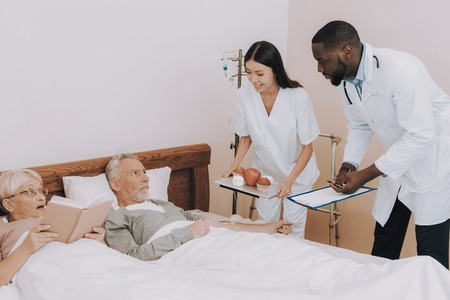 Medical Staff Offer Food Elderly Couple. Nurse Bring Apple and Muffins to Bed. Man Dripping. Elderly Couple Lay in Bed. Doctor with Papers. Nurse with Tray. Nursing Home. Patient Read Book.