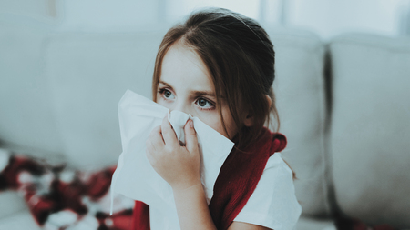 Little Girl with Cold Sitting on Sofa in Red Scarf. Sick Young Girl. White Sofa in Room. Unhappy Child. Disease Concept. Healthcare and Healthy Lifestyle Concept. Little Girl at Home.