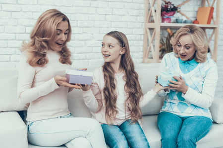Daughter Giving Gift Boxes to Family at Home. Mother with Daughter. Smiling Women. Celebration Concept. Happy Family. Sitting at Home. Holiday in March. White Sofa. Happy Grandmother. Stock Photo