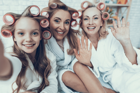 Smiling Women in White Bathrobes Taking Selfie. Happy Family. Mother with Daughter. Smiling Women. Smiling Grandmother. White Sofa. Family after Bath. Women's Beauty Concept. Using Smartphone. Banque d'images - 115666637