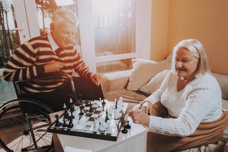 Senior Man and Woman Play Chess. Nursing Home. Man in a Wheelchair. Woman Covered with Blanket. Young Sear and Yellow Leaf. Senior Couple Hold Lees of Life. Retired People Smiling.