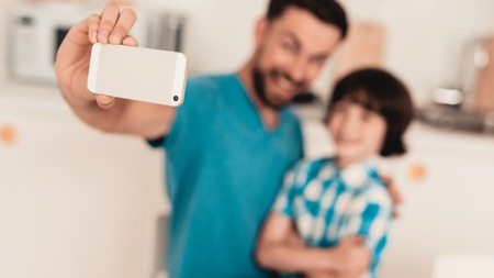 Happy Father and Son Using Smartphone at Home. Smiling Boy. Modern Kitchen. Sitting Boy. Boy in Shirt. Breakfast in Morning. White Table in Kitchen. Using Digital Device. Happy Family.