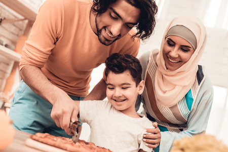Happy Arabian Family Eating Pizza in Kitchen. Muslim Family. Smiling Boy. Young Arabian Woman. Modern Kitchen at Home. Man Using Kitchenware. Young Family. Wooden Table in Kitchen. Food on Table. Archivio Fotografico