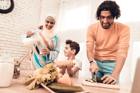 Happy Arabian Family Cooking Food in Kitchen. Muslim Family. Smiling Boy. Young Arabian Woman. Modern Kitchen at Home. Man Using Kitchenware. Young Family. Wooden Table in Kitchen. Food on Table. Stok Fotoğraf