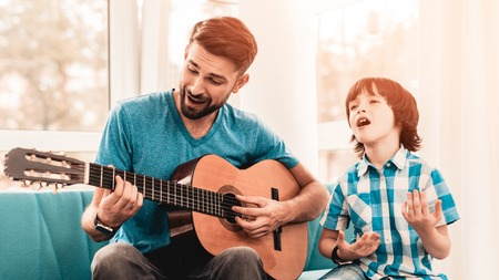 Young Bearded Father Playing on Guitar with Son. Happy Family Concept. Musician at Home. Young Boy in Shirt. Modern Hobby Concept. Music and Songs Concepts. Smiling Man.