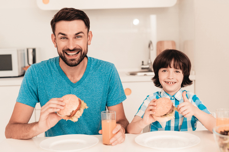 Smiling Son and Father Have Lunch in Kitchen. Boy in Shirt. Modern Kitchen. Sitting Boy. Boy with Spoon. Breakfast in Morning. White Table in Kitchen. Burger in Hands. Young Father.