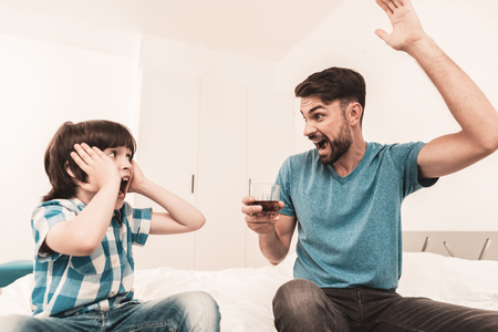 Little Boy Sitting in Room with Drunken Father. Crisis in Family. Alcoholism Problem Concept. Glass of Whiskey. Young Boy in Shirt. Modern Social Problems Concept. Sitting Sad Boy. Stock Photo