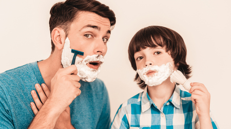 Young Father Teaches Little Son to Shave at Home. Foam on Face. Shaving Tool. Razor with Blade. Happy Family Concept. Young Boy in Shirt. Hygiene and Skincare Concepts. Hygienic Soap.