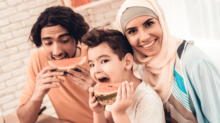 Happy Arabian Family Eating Watermelon in Kitchen. Young Boy. Young Arabian Woman. Modern Kitchen at Home. Man Using Kitchenware. Young Family. Lunch at Home. Food on Wooden Table.