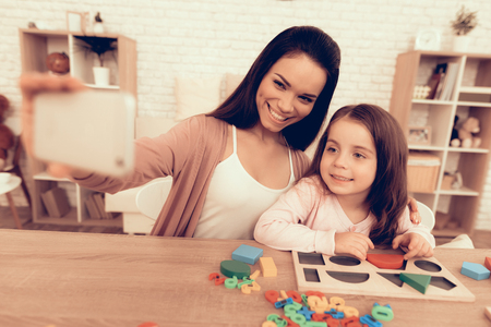 Mother Teaches Daughter. Educational Games. Learning Child at Home. Take Selfie. Child Development. Board Games for Children. Modern Learning for Children. Play Cubes. Wooden Figures and Board.