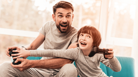 Father and Son Sitting and Playing on Console. Sitting Boy. Young Father. Playing on Console. Joystick in Hands. Young Bearded Man at Home. Sitting on Blue Sofa. Happy Family Concept. Stok Fotoğraf
