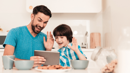 Happy Young Father and Son Using Tablet at Home. Smiling Boy. Modern Kitchen. Sitting Boy. Boy in Shirt. Breakfast in Morning. White Table in Kitchen. Using Digital Device. Happy Family.