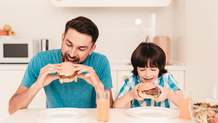 Padre e figlio sorridenti pranzano in cucina. Ragazzo in camicia. Cucina Moderna. Ragazzo seduto. Ragazzo con cucchiaio. Colazione al mattino. Tavolo bianco in cucina. Hamburger in mani. Giovane padre.