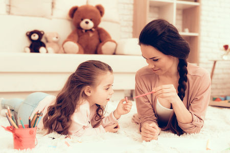 Fun with Daughter. Kids Home Games. Drawing with Pencils. Child Development. Mom and Daughter Play. Happy Mom and Child in Pajamas. Girl and Mother Lie on Carpet. Colour Pencils. Mom and Daughter Draw Stok Fotoğraf