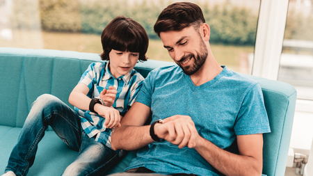 Little Boy with Father Wacthing on Hand Watches. Sitting Boy. Young Father. Young Bearded Man at Home. Sitting on Blue Sofa. Happy Family Concept. Time Concepts. Modern Hand Watch.