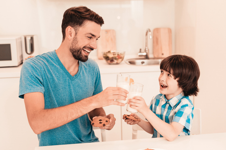 Smiling Son and Father Have Breakfast in Kitchen. Boy in Shirt. Modern Kitchen. Sitting Boy. Boy with Spoon. Breakfast in Morning. White Table in Kitchen. Gray Bowl on Table. Young Father. Stok Fotoğraf