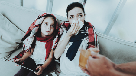 Sick Family Sitting on Sofa in Checkered Blankets. Mother and Daughter. White Sofa in Room. Unhappy Girl. Disease Concept. Healthcare and Healthy Lifestyle Concept. Using Serviettes. Girl with Laptop.