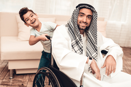 Young Arabian Man on Wheelchair with Smiling Son. Arabian Family Concept. Sitting on Wheelchair. Disabled Man. Smiling Boy. Sitting Muslim Man. Father and Son at Home. Happy Family. Banque d'images