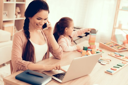 Mother Working at Home. Educational Games. Learning Child at Home. Child Development. Board Games for Children. Modern Learning for Children. Woman Working on Laptop. Girl Playing Educational Game.