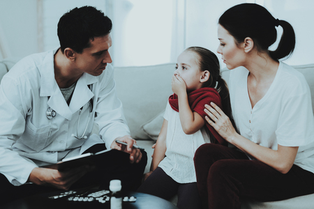 Doctor Visiting Little Girl in Red Scarf with Cold. Sick Young Girl. White Sofa in Room. Doctor in Uniform. Disease Concept. Healthcare and Healthy Lifestyle Concept. Mother with Daughter.