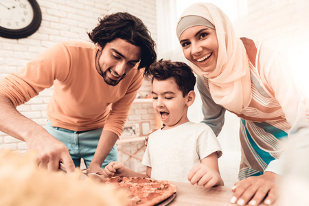 Happy Arabian Family Eating Pizza in Kitchen. Muslim Family. Smiling Boy. Young Arabian Woman. Modern Kitchen at Home. Man Using Kitchenware. Young Family. Wooden Table in Kitchen. Food on Table. Imagens