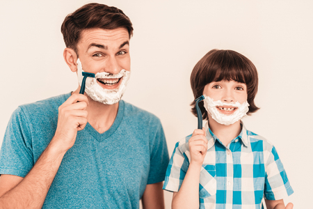 Young Father Teaches Little Son to Shave at Home. Foam on Face. Shaving Tool. Razor with Blade. Happy Family Concept. Young Boy in Shirt. Hygiene and Skincare Concepts. Hygienic Soap. Stock Photo