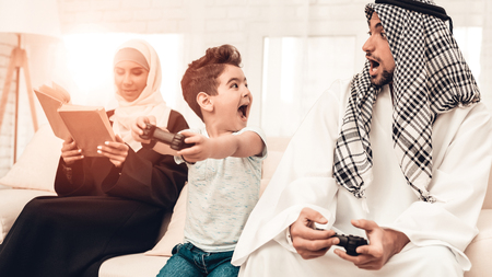 Happy Arabian Family Playing on Console at Home. Family Sitting on Sofa. Man Using Digital Device. Smiling Boay at Home. Muslim Family. Smiling Boy. Young Arabian Woman. Woman in Black Dress.