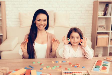 Spielzeugzahlen in den Händen. Lernspiele. Lernendes Kind zu Hause. Entwicklung des Kindes. Brettspiele für Kinder. Modernes Lernen für Kinder. Mädchen, das Zählung lernt. Alphabet lernen. Spielzeug Zahlen.