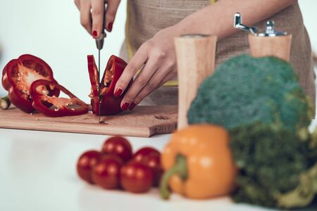 Female Hands Slicing Bell Pepper on Wooden Board. Stock Photo